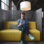 smart-young-man-sitting-casual-colorful-shoes-writing-office
