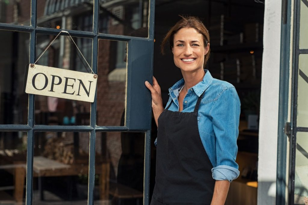 Portrait of a happy business owner standing at restaurant entrance.