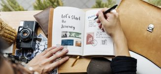 Young photographer writing diary and photobook