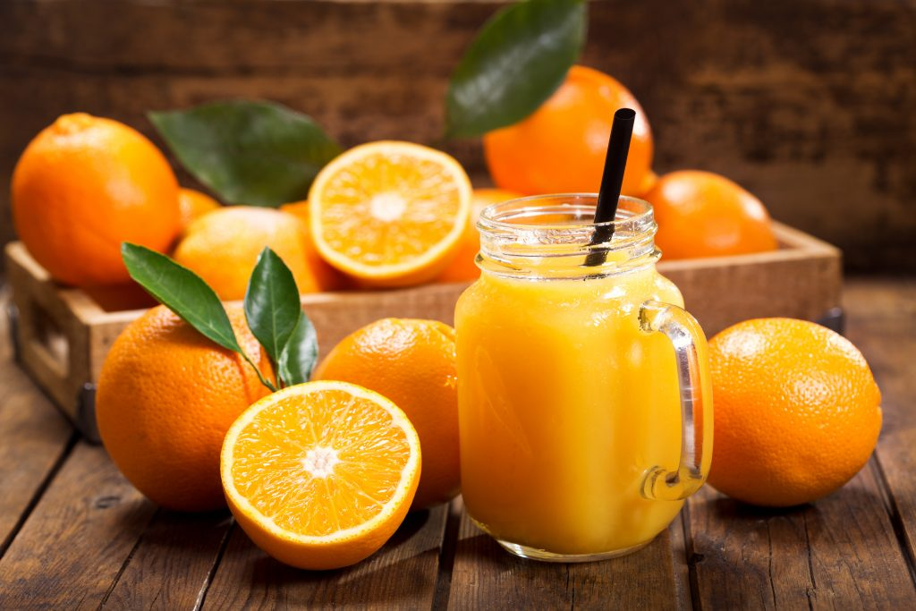 Oranges-on-a-wooden-table-with-a-glass-of-orange-juice